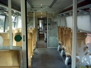 Espace pour les voyageurs, en 1ère classe. Moquette au sol et 3 places de front.